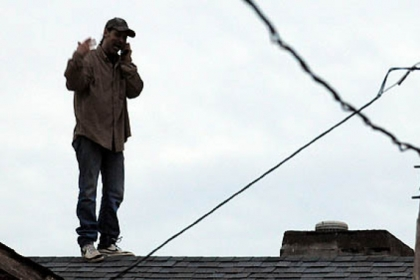 The man talks on his cellphone while standing on the roof of buildings between 54th and 55th streets in Lawrenceville.