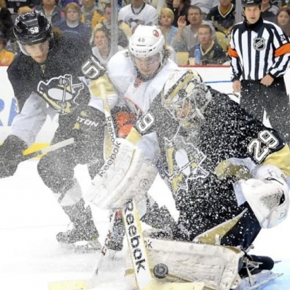 Goalie Marc-Andre Fleury somehow finds the puck through the ice storm kicked up by the Islanders' Michael Grabner in the second period Tuesday at Consol Energy Center.