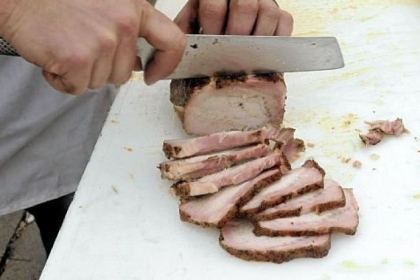 Slicing just-smoked pork loin at the smokehouse.