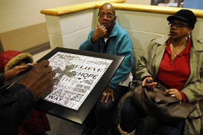 A memorial plaque is signed in memory of Isaiah Dent, 61, as 200 gathers at the community center of the Hays Manor housing development in McKees Rocks where Dent was found in his apartment beaten to death. Dent's sisters, Laverne Jackson of Wilmerding, left, and Carrol Dent of Youngstown, Ohio, watch the signing.