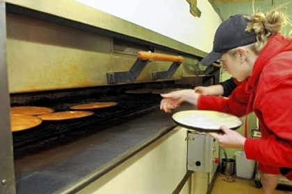 Alex Hill loads pizza crusts into the ovens at Augustine&#039;s pizza in New Castle, which makes between 2,400 and 3,000 crusts per day. The pizza is now sold at PNC Park, Giant Eagle and other venues.