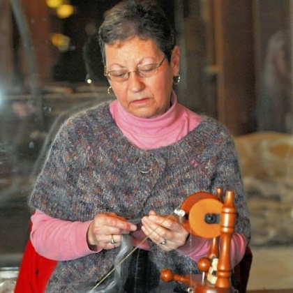 Lorraine Heasley from Hempfield, wearing her handmade sweater, spins yarn for another project.