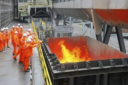 Officials gather to throw silver dollars into a carload of flaming coke fresh from the newly commissioned battery coke ovens following a ceremony at U.S. Steel's Clairton Plant. Casting silver dollars into faming coke is a long-held industry tradition when a coke oven battery is put into service.