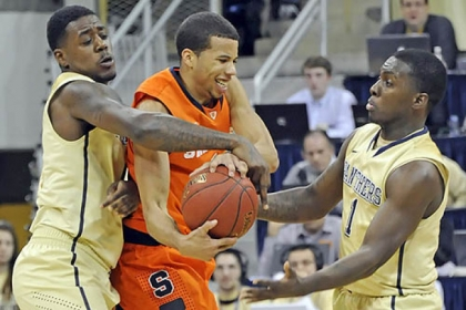 Pitt's Dante Taylor and Tray Woodall reach to steal the ball from Syracuse's Michael Gbinije in the second half at the Petersen Events Center this afternoon.