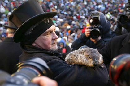 Groundhog Club Co-handler John Griffiths holds the weather predicting groundhog, Punxsutawney Phil, as he is surrounded by photographers at Groundhog Day festivities in Punxsutawney this morning.