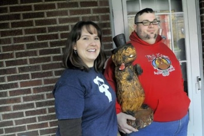 Deana Carpenter, left, and husband, Anthony Skariot, are the founders of the Outer Circle, a club that celebrates Groundhog Day all year round. Above, they pose with a wooden groundhog statue Wednesday at their Castle Shannon home.