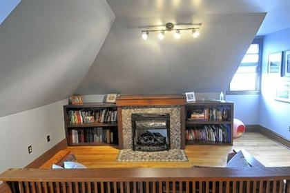In the third floor master suite of the Morningside Four-square, Chris Clarke forged a fireplace screen out of iron and built the bookcases. The handmade Amish settle, in the foreground, was a gift.