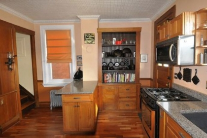 The remodeled kitchen has an original wooden cabinet that was covered in multiple layers of paint. It holds cast iron skillets and glass coffee percolators. The cabinet's lower half held a potato bin that is used as a recycling bin.