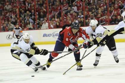 Washington Capitals left wing Alex Ovechkin (8) chases after the puck against Penguins right wing Craig Adams (27) and Kris Letang (58) during the first period.