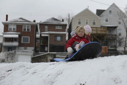 Sisters Ana Jean, 5, (right) and Magdalen McDermott, 4, prepare for a sledding run in their yard in Greenfield on Sunday.