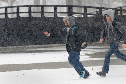 Patrick Terry and Eli McCary walk through the snow at Point State Park during today's snowfall