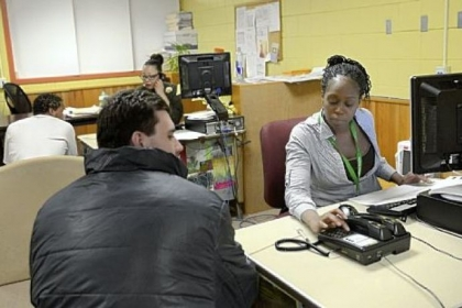 Discharge and release coordinators Asia Pruden, foreground, and Ronele Thomas process former inmates at the Discharge and Release Center on Thursday at the Allegheny County Jail in Pittsburgh.