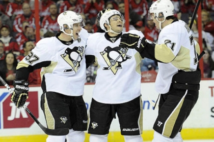 Penguins left winger Chris Kunitz, center, celebrates his goal in the second period with teammates Sidney Crosby, left, and Evgeni Malkin in Washington Sunday. Kunitz had a hat trick with goals in the second and third periods.