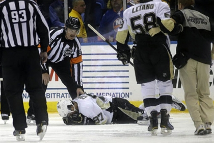 Penguins center Sidney Crosby lies on the ice after he was hit in the face in the second period against the Islanders.