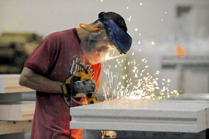 Tony Carper grinds the edges of a steel-reinforced thermal building panel after it was cut for a customer order at Syntheon's Leetsdale facility. The former Nova Chemicals company makes cast panels and concrete additives using polystyrene.