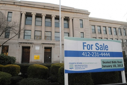 "A ""For Sale"" sign stands in front of the former Pittsburgh Schenley High School."