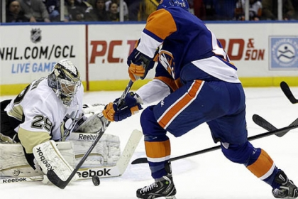 Penguins goalie Marc-Andre Fleury makes a save as Islanders center Keith Aucoin skates in front of the crease in the second period.