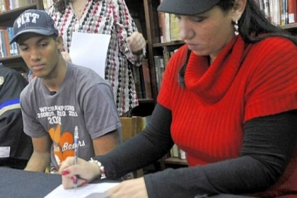 Tyler Boyd, left, watches as his mother Tonya Payne puts her signature on his letter of intent to play football for the University of Pittsburgh.