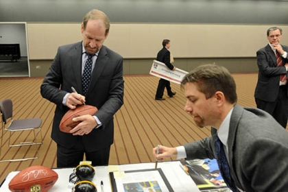 Former Steelers Coach Bill Cowher signs a football to be auctioned off for charity.