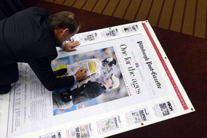 Former Steelers Coach Bill Cowher signs a large replica of the Post-Gazette edition of his Super Bowl victory to be auctioned off for charity.