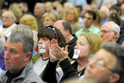 Lisa DeSantis, left, of New Castle and Maggie Henry of Bessemer cover their mouths with Ban Fracking Now stickers during a hearing about the county's deal with Consol Energy to extract natural gas from land at Pittsburgh International Airport.