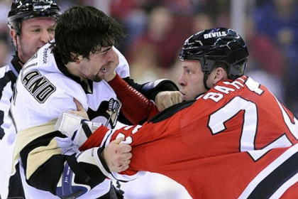 The New Jersey Devils' Krystofer Barch, right, fights with the Penguins' Deryk Engelland during the first period of this afternoon's NHL hockey game in Newark.