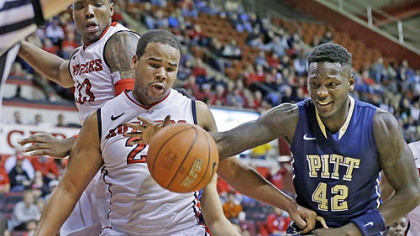 Pitt's Talib Zanna grabs for the ball in front of Rutger's Austin Johnson during the first half of today's basketball game in Piscataway, N.J.