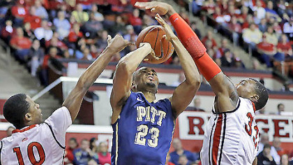 Pitt's Trey Zeigler has his shot blocked by Rutgers defender Wally Judge (33) as Rutgers' Mike Poole (10) helps out during the first half of today's basketball game in Piscataway, N.J.