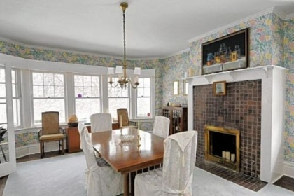 The dining room's architectural features include crown molding. The fireplace, one of many in the home, is decorative.