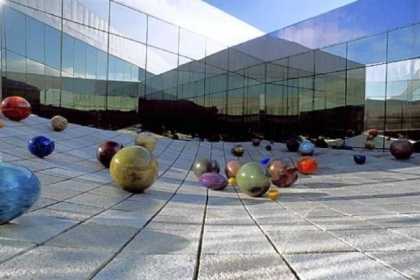 "Richard Rhodes' untitled ""stone wave"" sculpture at Tacoma Art Museum is decorated with Ma Chihuly's Floats (in honor od Dale Chihuly's mother) during the summer months."