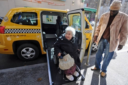 Lucy Spruill of Squirrel Hill rolls down the ramp from her taxi ride to Market Square with driver Eddie Green Monday.