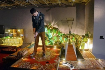 Nick Barletta putts in a mini-golf game at PLAY Parlour.