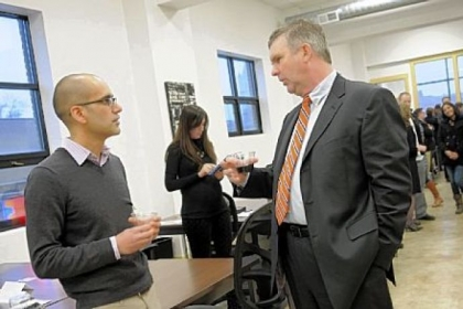 Anup Aryal, left, with the startup Open Curriculum, talks with Tim Devlin, a program director at Allegheny Intermediate Unit, at the grand opening of the Hustle Den Wednesday in East Liberty.