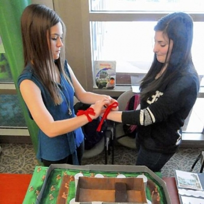 "Rachel Kozemchak, left, and Brittany Berg fasten their ""revolutionary ribbons"" as they wait for visitors to their Storming of the Bastille Prison exhibit at the ""Tale of Two Cities"" Museum staged by Leticia Harshman's ninth-grade English classes at Pine-Richland High School."