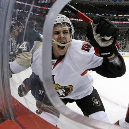 Ottawa Senators defenseman Erik Karlsson, center, grimaces as he hits the boards after colliding with Penguins left wing Matt Cooke Thursday night.