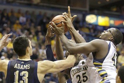 Pitt's Steven Adams fights for a rebound with Marquette's Steve Taylor Jr. and Chris Otule, right, during the first half of today's game in Milwaukee.