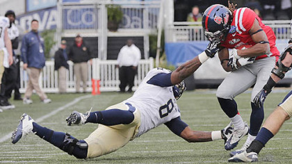 Pitt linebacker Todd Thomas grabs the face mask of Mississippi running back Jeff Scott in the first quarter of the BBVA Compass Bowl.