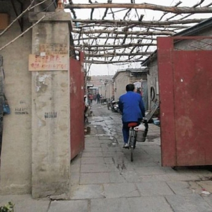 A man bicycles down an alley in a migrant neighborhood about an hour's drive from central Beijing. Families stay in meager dwellings until their jobs in the city, as hotel maids or street sweepers, can buy them better places to live.