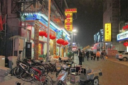 Although Beijing is full of cars, many Chinese in the Wangfujing shopping district still get around on bicycles.