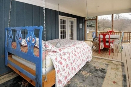 The enclosed rear porch with swinging bed is off the first-floor master bedroom.