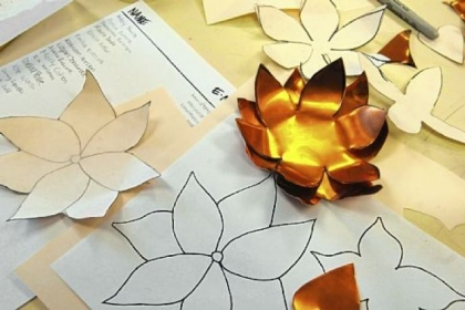 Paper patterns are used to create flowers from copper.