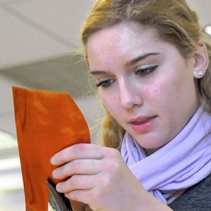 Student Emilia Riccinti fashions a flower petal from a copper sheet.