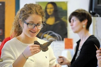 Student Alana Rascoe admires the butterfly she has created from a copper sheet.