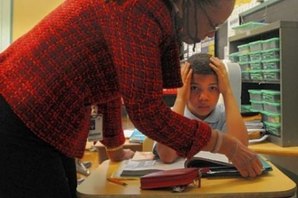 Second-grader Aundra Payne looks up as superintendent Linda Lane asks him about what he is reading at Pittsburgh Morrow PreK-6 in Brighton Heights.