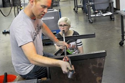 Dana Laskowski, a teaching assistant at the Pittsburgh Glass Center who began taking classes while a student at CAPA, delivers air to the project upon which teacher Jason Forck is working.