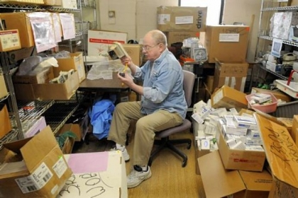 Jim Carr of Shaler, a retired phone company technician, checks and fixes blood pressure monitors in a back room of Global Links in Garfield. Mr. Carr volunteers at Global Links four to six hours a week.