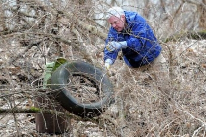 Retired volunteer John Cokley picks up litter on a hillside above Steuben Street in Pittsburgh?s West End.