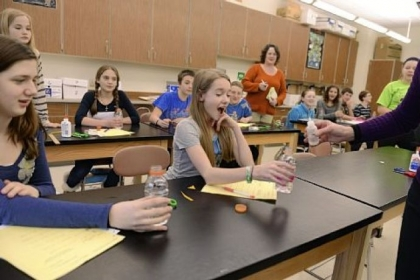 "Seventh-grade science teacher Angela Lamers, far right, tests students Gwen Koladish, 12, center, and Lilli Horvat, 13, to see if their plastic bottles have become ""infected"" Wednesday at Hampton Middle School. Students participated in a simulated outbreak in which they were exposed to various contagions. Students then researched their ""infections."""