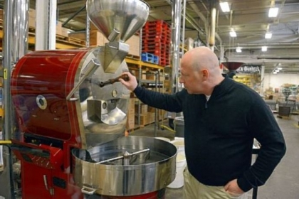 Bill Swoope Jr., owner of Coffee Tree Roasters, checks on the beans being roasted at the company's facility in West Mifflin.