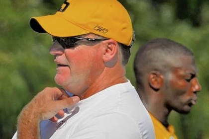 Kevin Colbert, General Manager of the Pittsburgh Steelers surveys a training camp practice in 2011 while safety Ryan Clark walks by behind him.